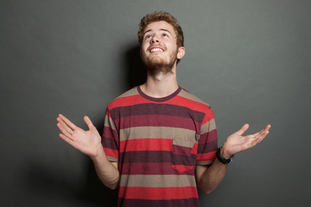 disbelief: Young man adult caucasian man in casual clothes and scruffy beard on a grey background - Arms out in disbelief