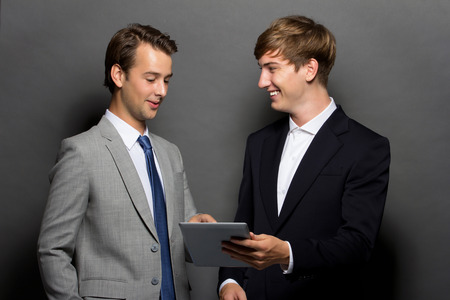 a potrait of Two young man discuss something on the tablet