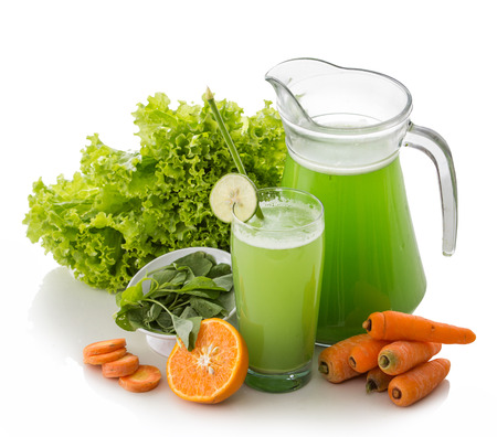 A potrait  of a glass carrot, lettuse, and spinach mix juice