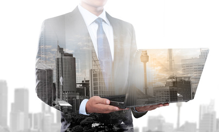 도시와 사업가의 이중 노출 랩톱 컴퓨터를 사용