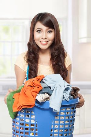 woman doing a housework holding laundry Reklamní fotografie