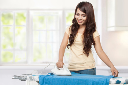 mother board: Smiling young woman ironing clothes at home