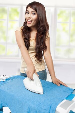 woman ironing: Smiling young woman ironing clothes at home