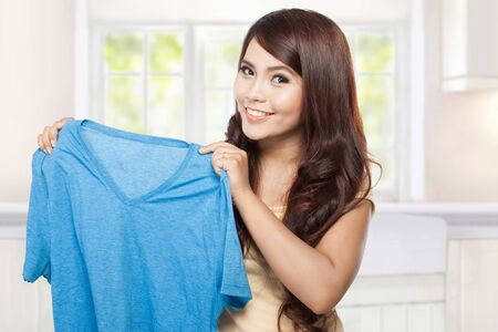 clean clothes: young smiling asian woman showing blue clean clothes Stock Photo