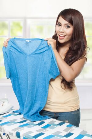 clean clothes: young smiling asian woman showing white clean clothes Stock Photo
