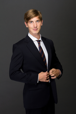 neck tie: a potrait of a smiling young man in black suit with a neck tie while buttoning the blazer