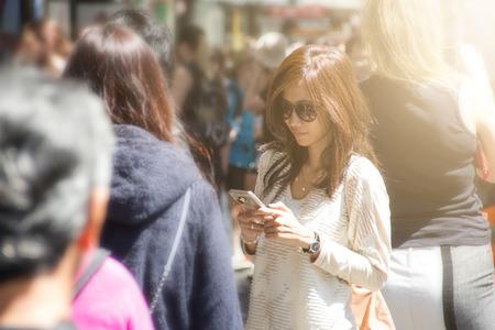 vrouw met behulp van een slimme telefoon in de straat vol met publiek