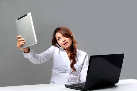 outworking: A portrait of a young asian businesswoman looking at a tablet while speaking on the phone beside a laptop