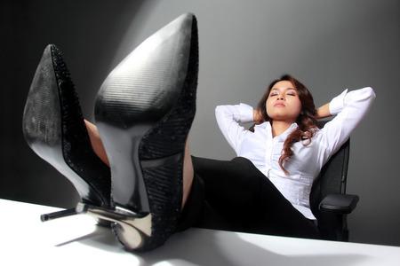 piernas con tacones: Un retrato de una joven empresaria con las piernas cruzadas sobre la mesa, descansando Foto de archivo