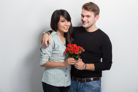 propose: A portrait of a multicultural couple. boy friend give her red roses