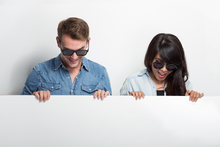 blank poster: A portrait of Happy Young Multiculture Couple with white blank billboard isolated