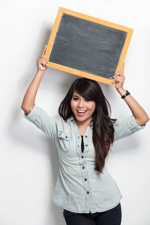 A portrait of a young asian woman holding blank black board photo