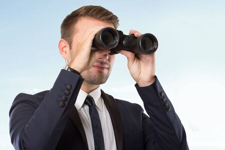 A portrait of a young businessman looking through binoculars - market research concept Banque d'images
