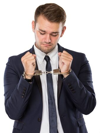 cuffed: A portrait of a youbg bussinessman with handcuffs over hands Stock Photo