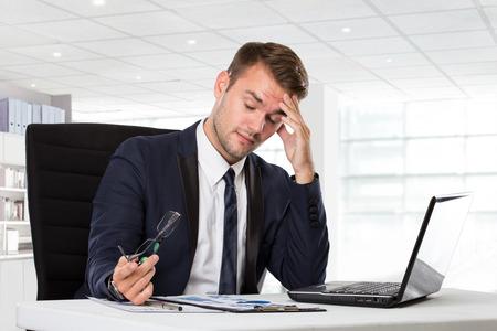 dolor de cabeza: Un retrato de un hombre de negocios joven que tiene dolor de cabeza, destacó con su trabajo