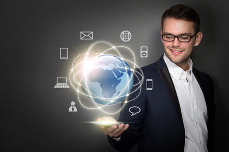 world economy: young businessman connected through cellphone on his hand. virtual hightech concept Stock Photo