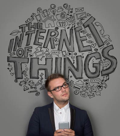 'young things': A portrait of a young businessman with a cellphone. the internet of things concept