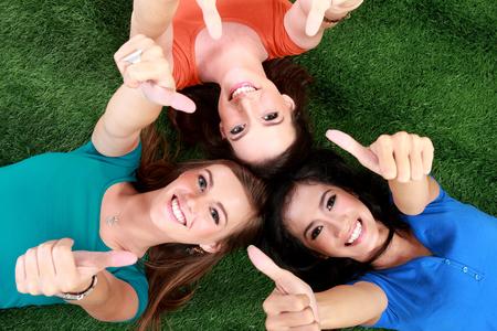 tumb: Three happy teenage girls smiling lying on the grass showing thumb up Stock Photo