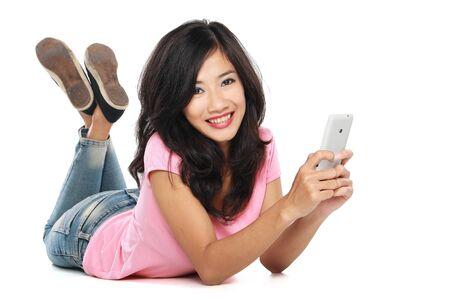 глядя на камеру: Красивая улыбается женщина с handphone расслабляющий на полу, глядя на камеру
