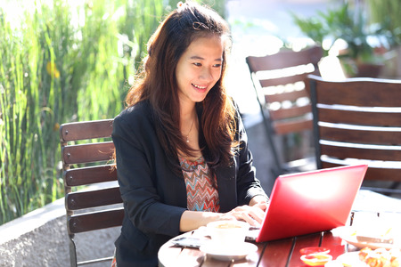 search the internet: A portrait of a Young businesswoman work oudoor, in a cafe