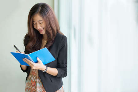 portrait of a young asian business woman writing a note photo