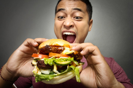 A portrait of young man have a great desire to eat a burger 스톡 콘텐츠