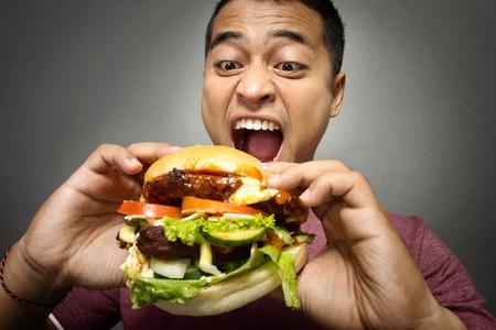 comiendo: Un retrato de hombre joven y tiene un gran deseo de comer una hamburguesa Foto de archivo