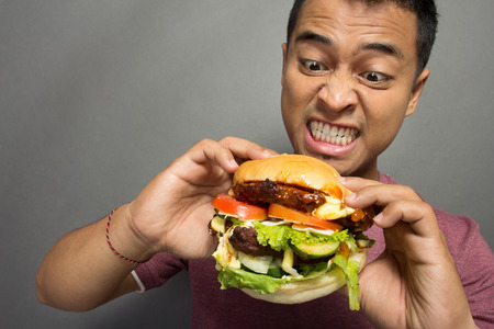 adult sandwich: A portrait of young man have a great desire to eat a burger Stock Photo