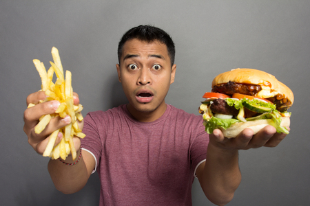 A portrait of a young man surprised with the size of his burger portion package photo