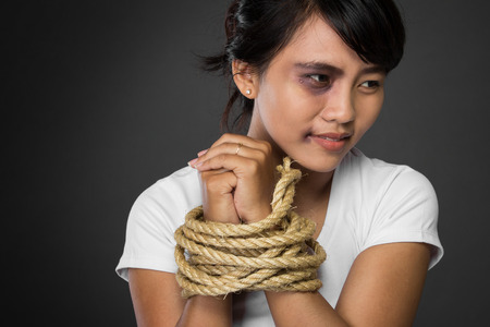 woman tied: A portrait of a woman with hands tied up with rope being abused,   struggle, terrified,  and threaten from domestic violence and abuse Stock Photo