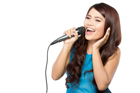 A portrait of a young woman sing holding a mic, isolated white background Stock Photo