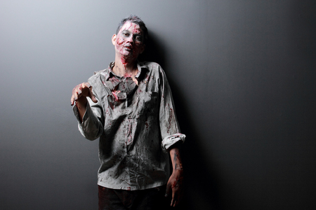 Zombie standing with black background hand up scaried photo