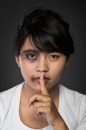 beaten: A portrait of close up of an asian girl. Holding her finger, showing to keep silent.