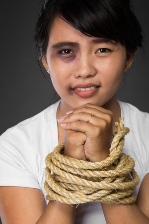 A portrait of a woman with hands tied up with rope being abused,   struggle, terrified,  and threaten from domestic violence and abuse photo
