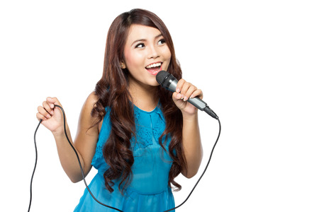 A portrait of a young woman sing holding a mic, isolated on white background