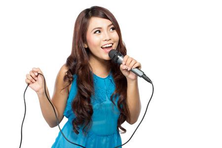 cantando: Un retrato de una mujer joven canta sosteniendo un micrófono, aislado en fondo blanco