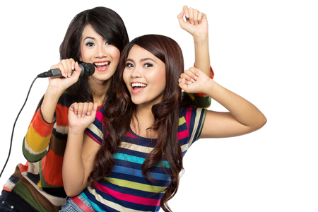 karaoke singer: A portrait of two asian girls in striped t-shirt singing together