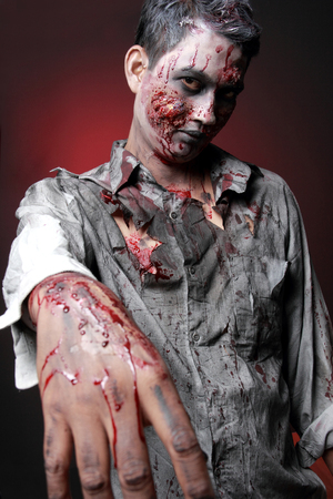Zombie standing rise hand and looking camera photo