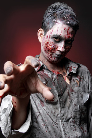 Portrait of a Zombie standing looking camera with claw photo