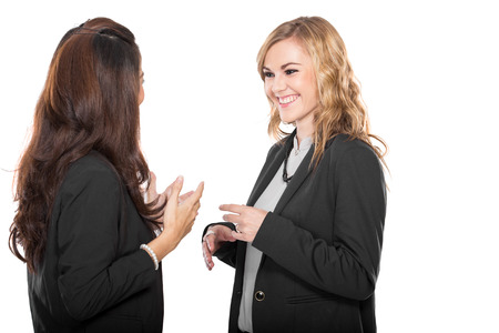 A portrait of two happy young businesswoman talking, isolated