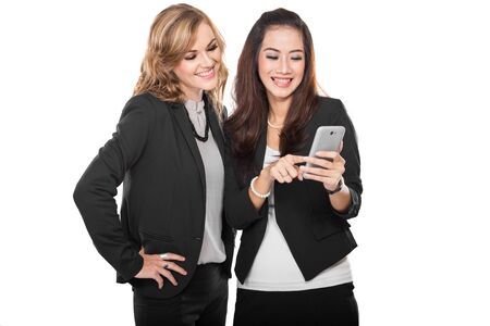 A portrait of two young businesswoman talking about something in the cellphone photo