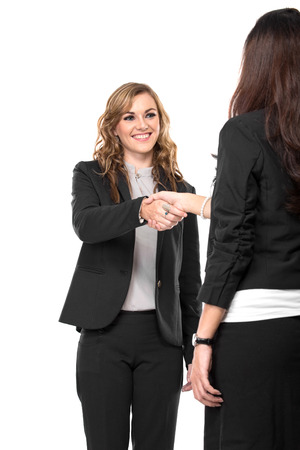 A portrait of a two young businesswoman making a deal and shaking hands isolated on a white background photo