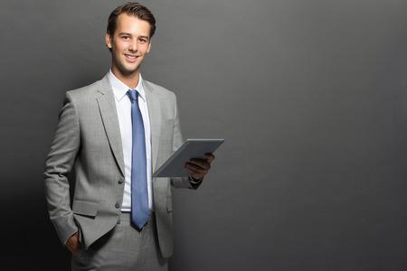 태블릿 성공적인 유럽 비즈니스 남자의 초상화는 검은 배경 위에 절연