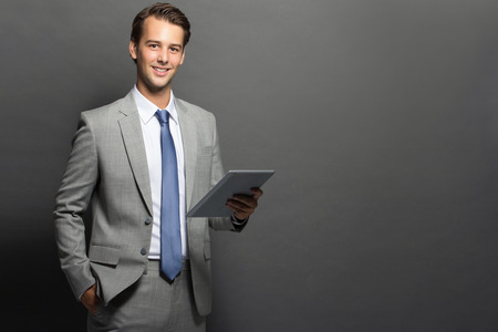 european: Portrait of a successful european business man with tablet isolated over black background Stock Photo