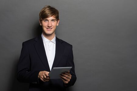 considerate: Portrait of a successful business man with tablet over grey background Stock Photo