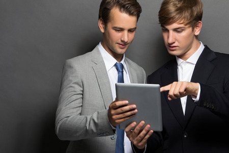 considerate: Portrait of a successful two business man with tablet isolated over black background