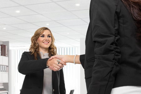 A portrait of a two young businesswoman making a deal and shaking hands photo