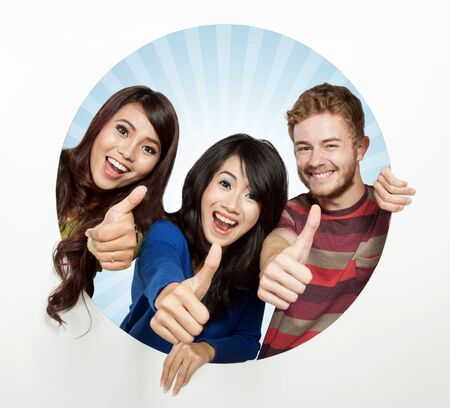 A portrait of three happy student come out from a white circle, thumbs up photo