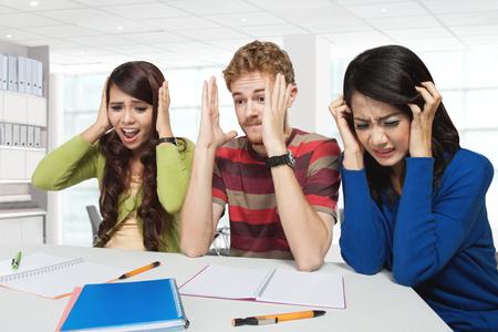grupo de hombres: Un retrato de tres jóvenes estudiantes de estrés sentados juntos