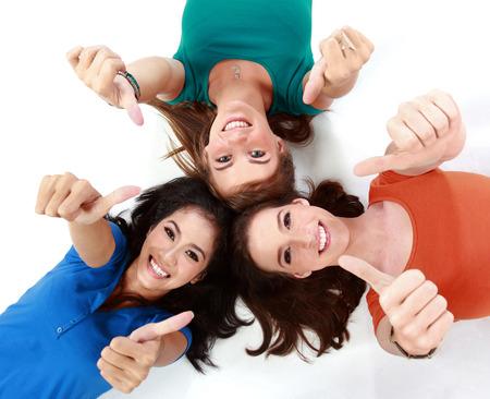 tumb: Three happy girls smiling lying on the floor showing thumb up Stock Photo